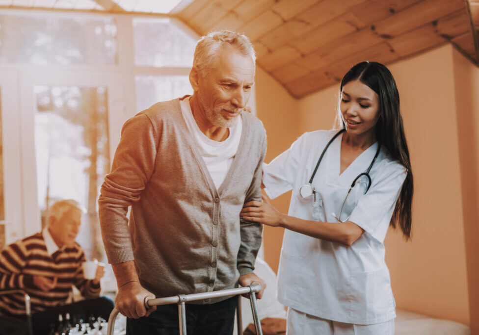 Doctor Supports Man. Pensioner on Go-Carts. Caregiver. Adult Caucasian. Asian Nurse. Helps. Adult Walker. Nursing Home. Hard Go Himself. Nurse Hold. Old Bones. Chair Days. Retired. Medical Therapy.