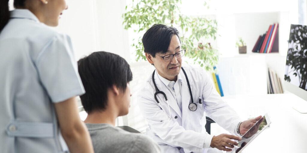 タブレットで現在の状況を確認する主治医と患者