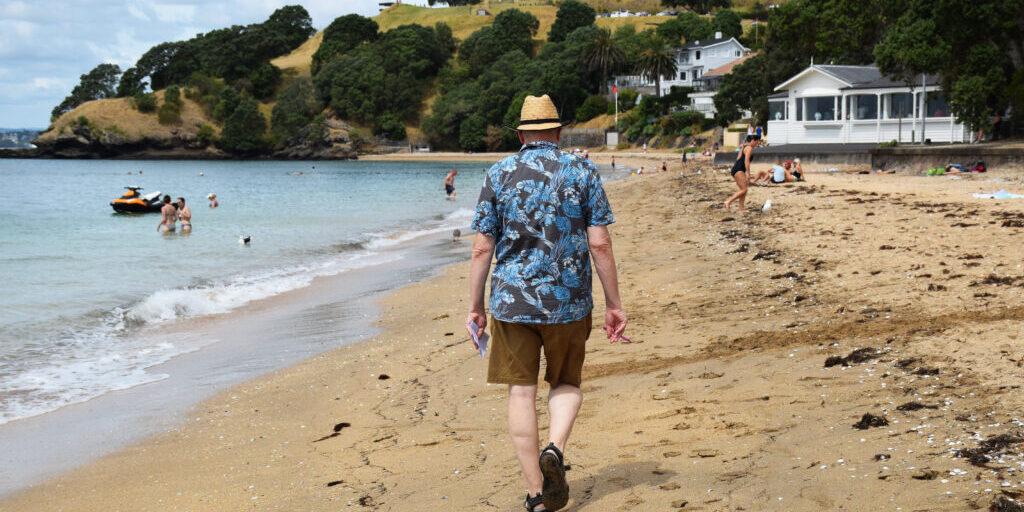 Old man walking away down the beach