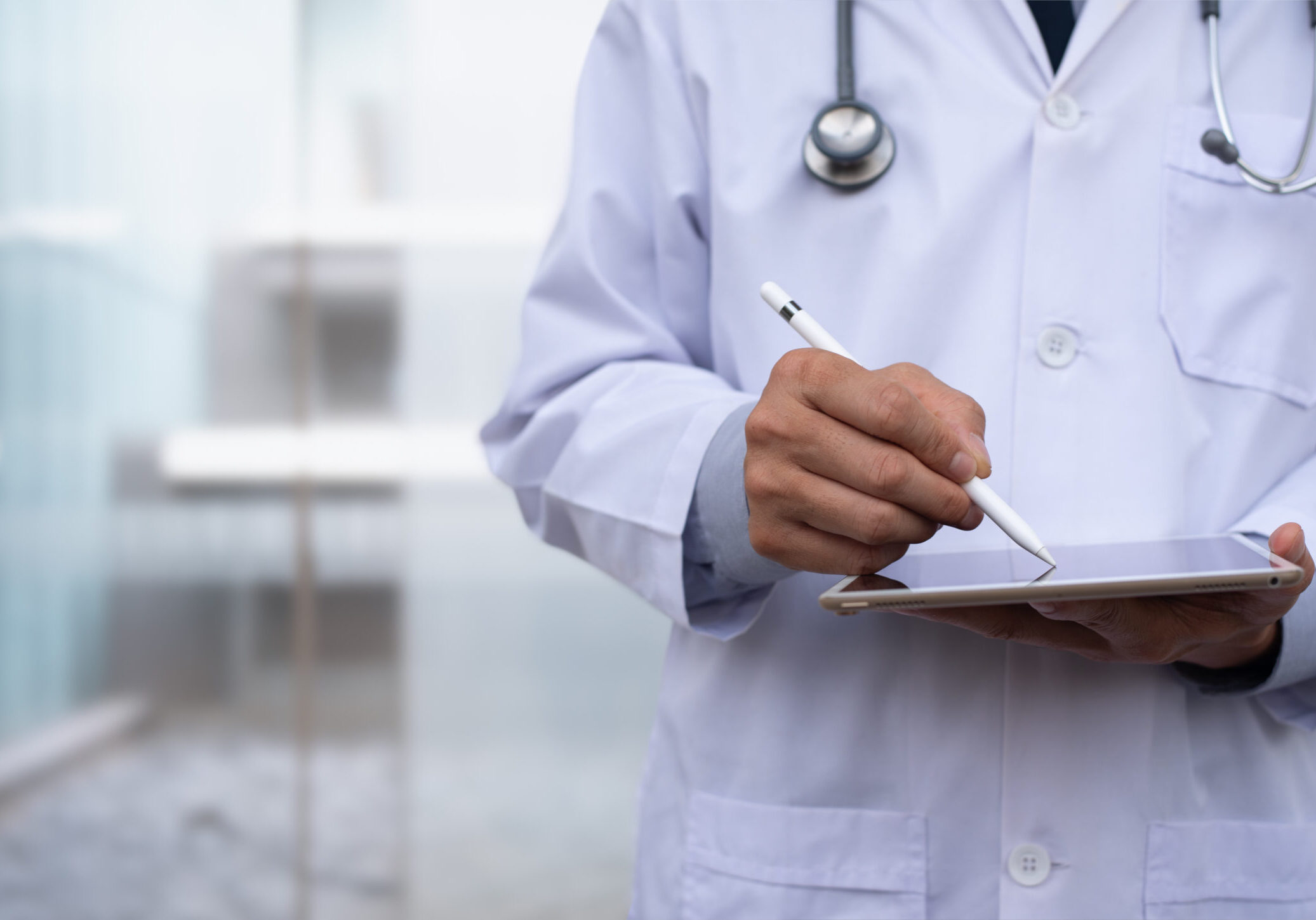 Doctor using electronic pen on  digital tablet, reviewing  medical record wrting prescription on digital document with hospital background, Electronic medical record system, health and technology, telemedicine concept