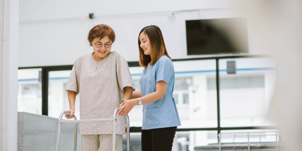young physical therapist helping senior patient in using walker during rehabilitation