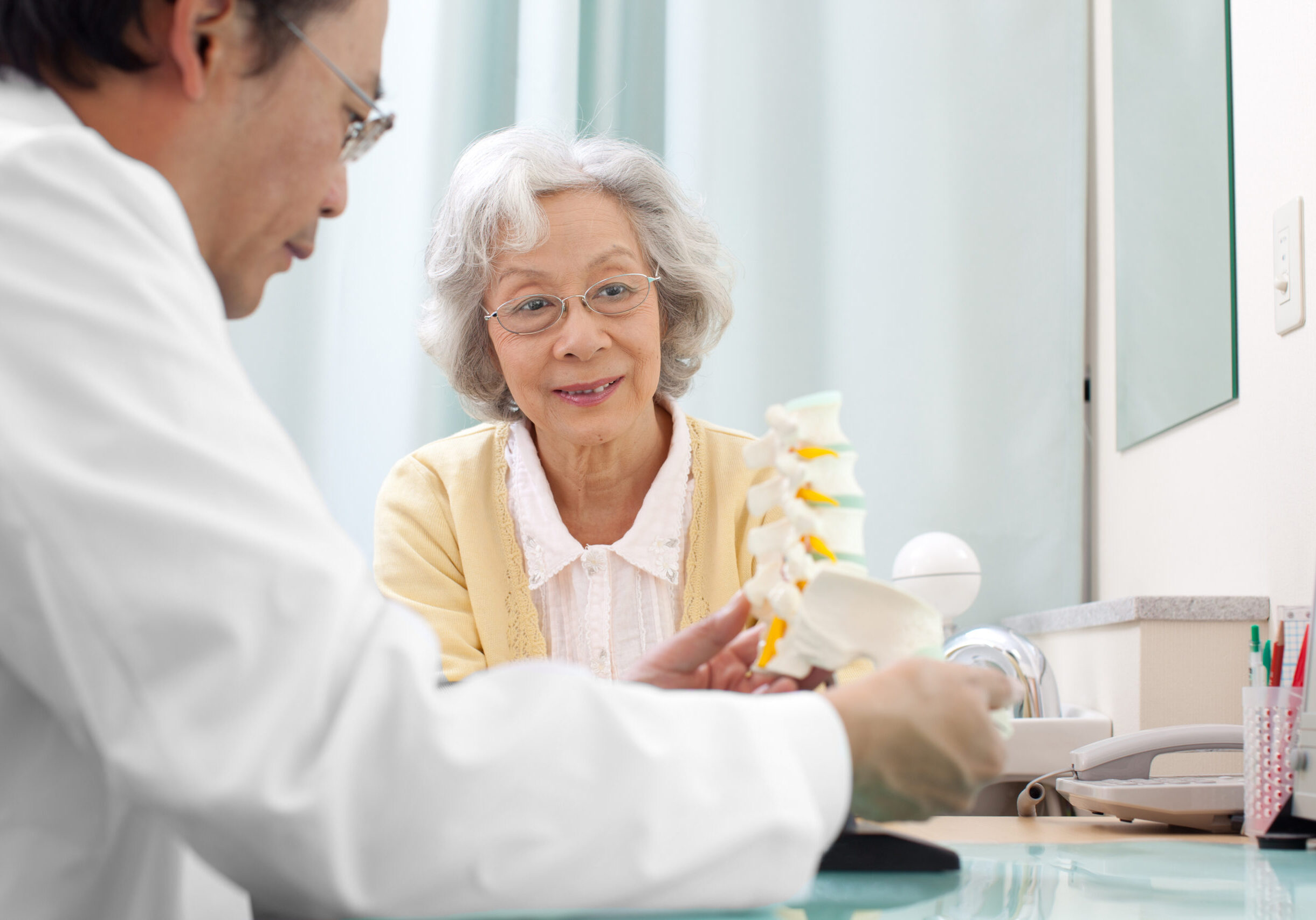 Senior woman visiting the doctor in his office. Doctor explaining spine problem to her using a bone model.